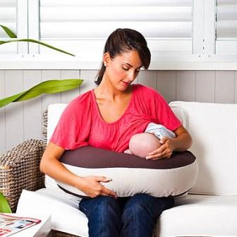 mum using milkbar portable twin nursing pillow on lounge