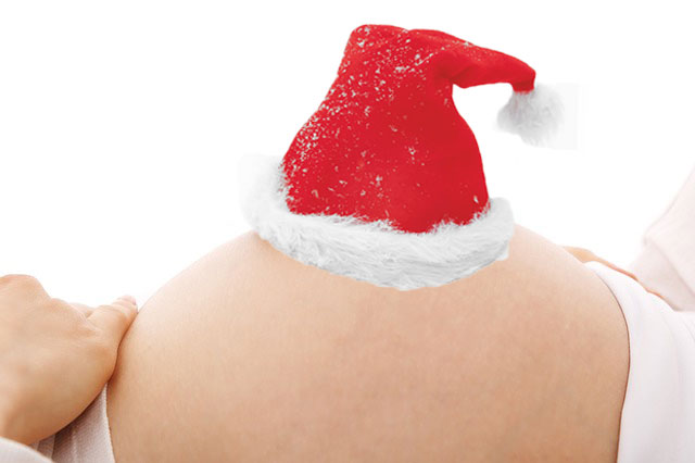 pregnant bump wearing a santa hat for the festive season