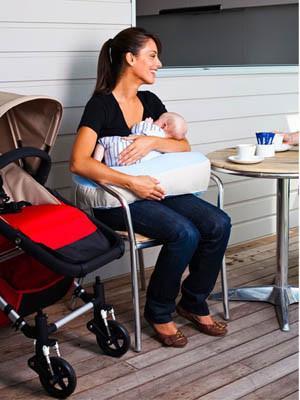 mum using breastfeeding pillow to nurse her baby