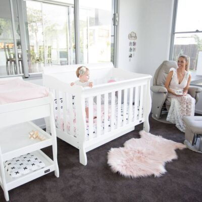 cot in bedroom setting with baby inside