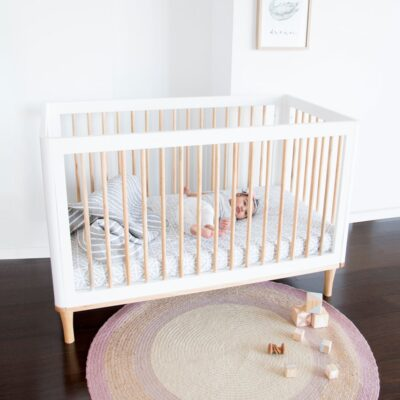 riya cot in white with baby inside