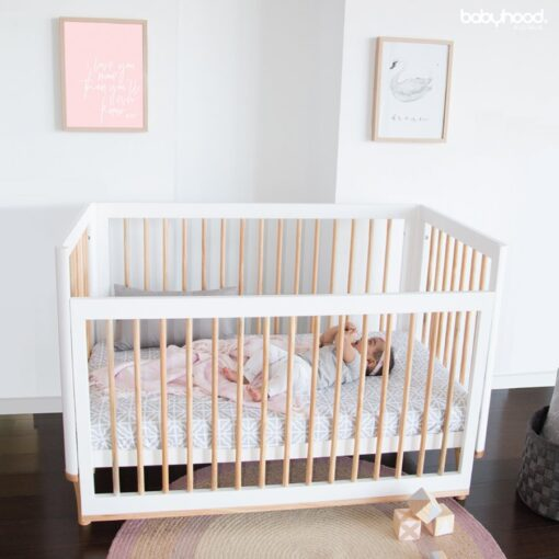 riya cot in white and natural with baby