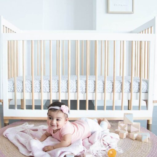 Riya cot in white with baby in front